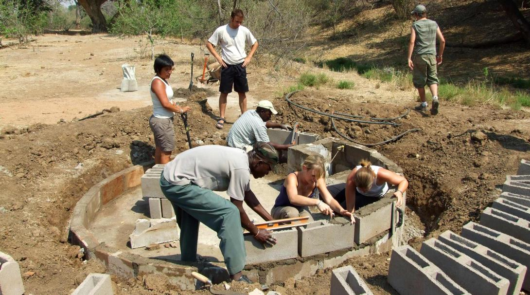 Teenage volunteers working on wildlife conservation by building water holes.